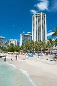 Tourist Sunbathing And Surfing On Waikiki Beach On Hawaii Oahu