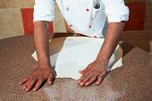 hand of chef baker in white uniform making pizza at kitchen