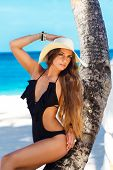 A Beautiful Young Woman With Long Hair In A Straw Hat Relaxes On The Palm Sea In The Background