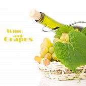 Cluster Of Grapes In Wicker Basket With Wine Bottle Behind It