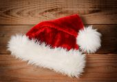 Santa Claus Hat on a rustic wooden floor with an instagram retro look. High angle view with vignette