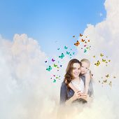 Happy mother with daughter sitting on clouds