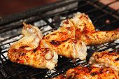 bbq grill meat - ready chicken wings on grid over charcoal