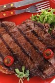 new york meat style beef steak fillet on red plate with hot chili pepper and green salad isolated ov