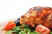 poultry : fresh grilled whole chicken with black olives and raw tomatoes on wooden board isolated ov