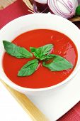 cold fresh diet tomato soup with basil thyme and dry pepper in big bowl over red mat on wood table r
