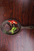 fresh roast beef fillet mignon on old retro style cast iron pan on retro wooden table as background