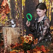 An attractive elementary girl viewing  a chipmunk through her magnifying glass.  They're in a woods
