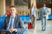 Happy businessman with touchpad looking at camera with his partners walking on background at the air