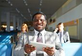 Young African-american businessman with touchpad sitting in airport with two colleagues on backgroun