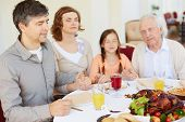 Family of four praying at festive table on Thanksgiving day, focus on young man