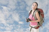 Happy smiling Asian young female backpacker with camera standing in front of blue sky.