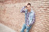 Picture of a young handsome man leaning on a brick wall while fixing his hair, with one hand in the