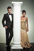 attractive elegant couple posing near column in studio, woman looking down