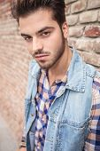 Close up picture of a handsome man looking at the camera, near a brick wall.