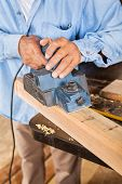 Midsection of senior carpenter shaving wood with electric planer in workshop