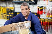 Portrait of mature worker lifting tool package in hardware shop