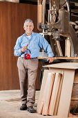 Full length portrait of senior male carpenter holding ear protectors by bandsaw in workshop