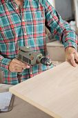 Midsection of carpenter using electric drill in workshop