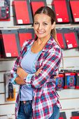 Portrait of confident female customer standing arms crossed in hardware store