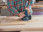 Midsection of male carpenter using electric planer on wooden plank at workshop