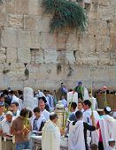 JERUSALEM, ISRAEL - SEPTEMBER 20, 2013:The Western Wall of the Temple in Jerusalem. Many religious Jews in traditional robes tallit gathered for prayer. Morning Sukkot