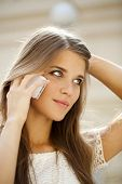 Portrait of a beautiful young woman calling by phone indoor