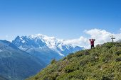 COL DE BALME, FRANCE - SEPTEMBER 01: Backpacker stretching and looking at view with Mont Blanc in th