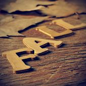 wooden letters forming the word fall and some autumn leaves on a weathered wooden background