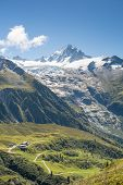 Chalets at the bottom of massive Tour Glaciers, in France.