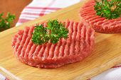 detail of two raw hamburger patties with parsley on wooden cutting board