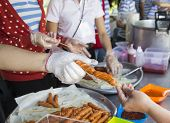 People's Hand Is Taking Fried Sausage Stick