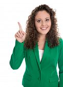 Isolated smiling young businesswoman in green presenting with finger.