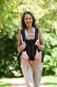 Happy Mother Walking With Infant In Baby Carrier