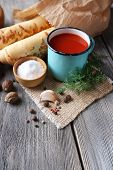 Homemade tomato juice in color mug, bread sticks, spices and fresh tomatoes on wooden background
