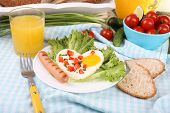 Scrambled egg with sausage and vegetables served in plate on fabric background
