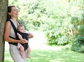 Mother Smiling In Park With Baby In Sling