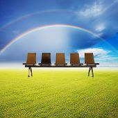 chair and  grass field with rainbow in the sky