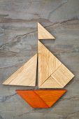 abstract picture of a sailing boat built from seven tangram wooden pieces over a slate rock backgrou