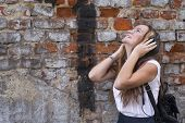 Young emotional girl enjoying music with headphones on the brick wall background.
