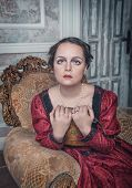 Beautiful Woman In Red Medieval Dress On The Armchair