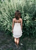 Curly Woman Backside on White Dress, Facing Huge Green Plants