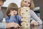 Family playing with wooden blocks at home