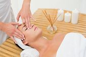 Peaceful brunette enjoying a face massage in the health spa