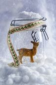 Reindeer figure in glass jar with falling snow