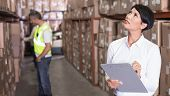 Постер, плакат: Pretty warehouse manager checking inventory in a large warehouse