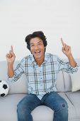 Portrait of a happy soccer fan cheering while watching tv