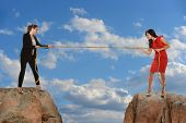 Business concept - Two businesswomen standing on rocks pulling on rope