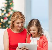 christmas, x-mas, happiness, modern technology concept - mother and daughter with tablet pc