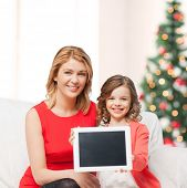 christmas, x-mas, happiness, advertisement concept - mother and daughter with tablet pc showing blan